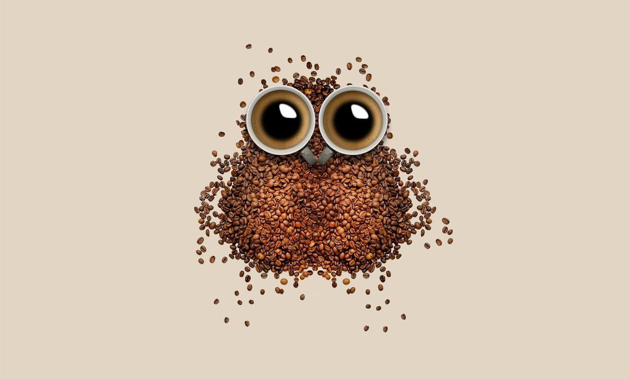 coffee beans and mugs forming owl shape on table