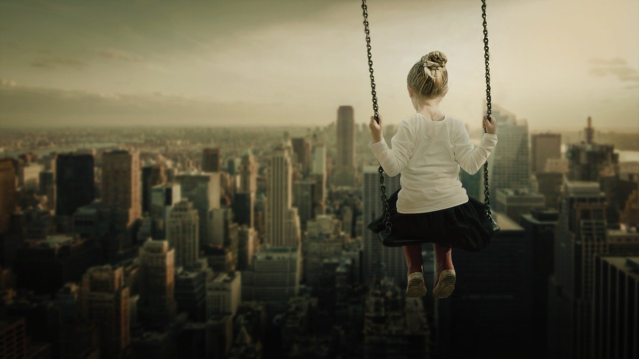 girl on swing high over city scape