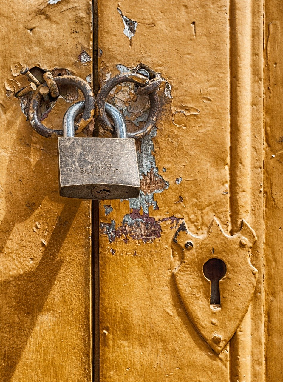 Padlock on door with keyhole and peeling paint
