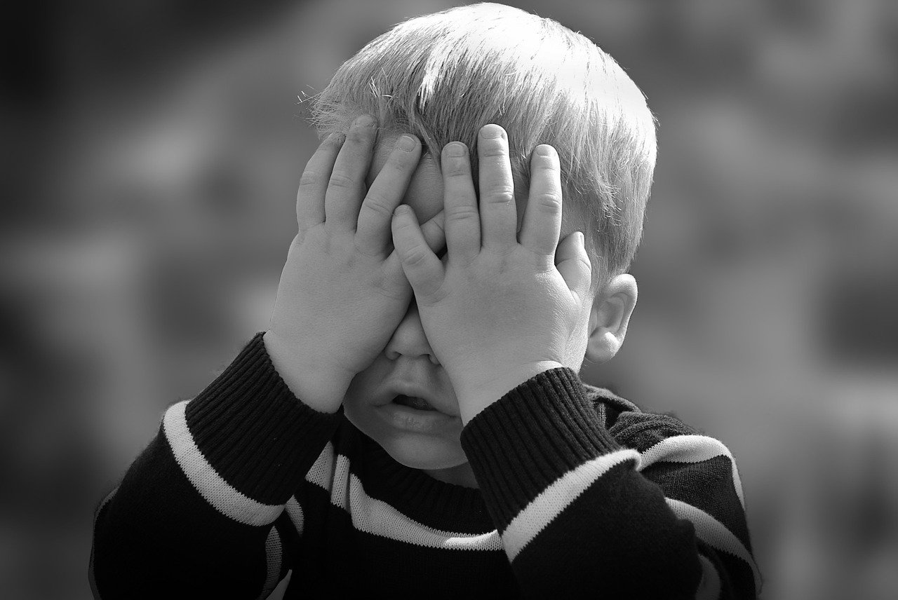 child covering face in embarrassment