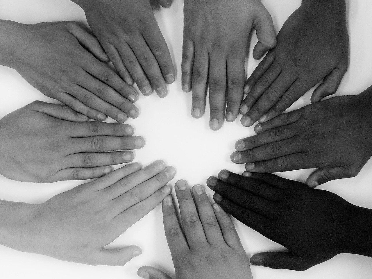 people's hands forming a circle, different skin colors