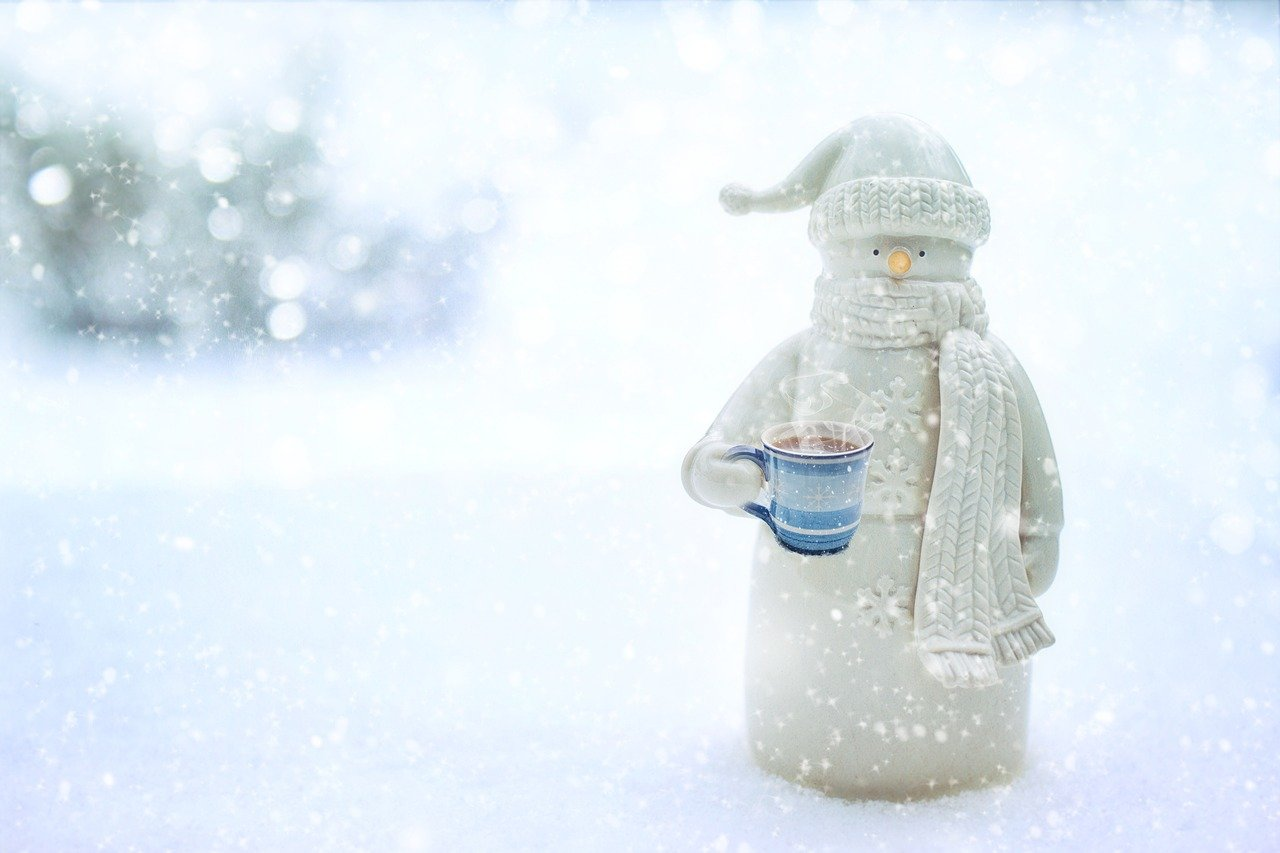 Tall snowman with scarf, hat, and mug of coffee