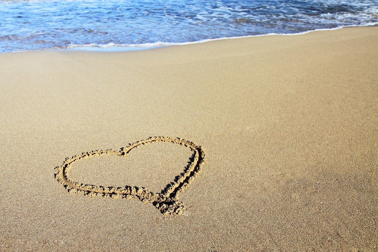 heart drawn in sandy beach with waves