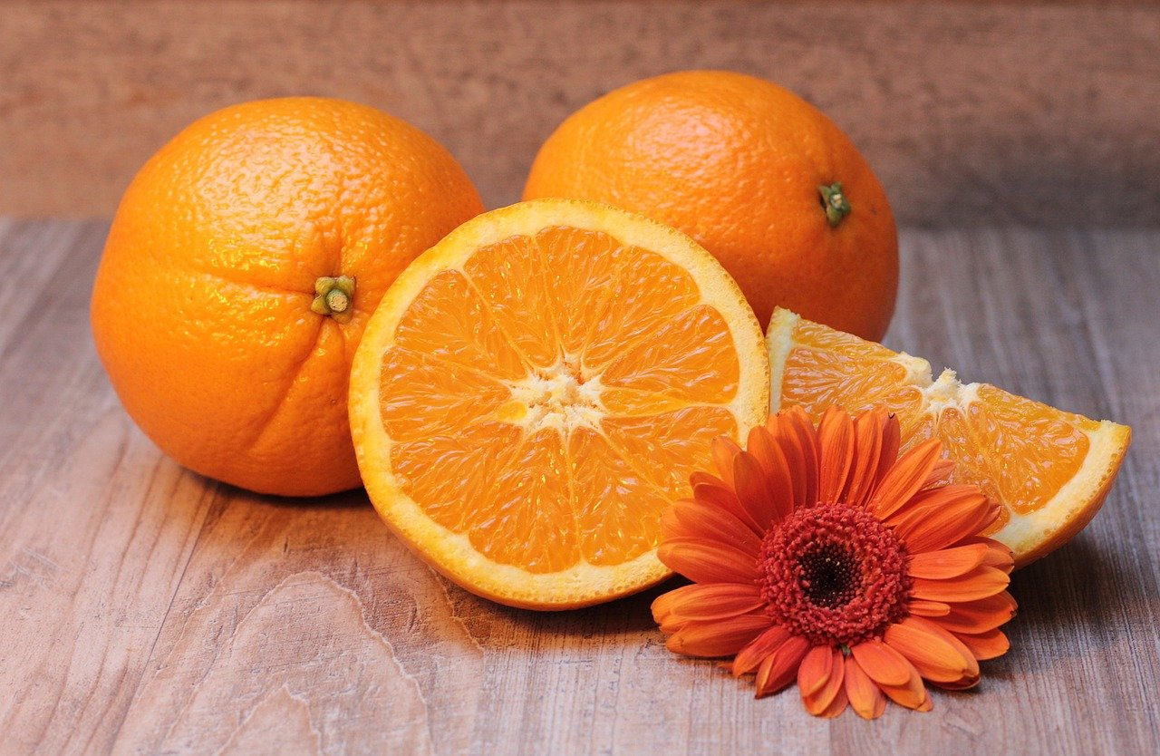 oranges and orange daisy on a wood table
