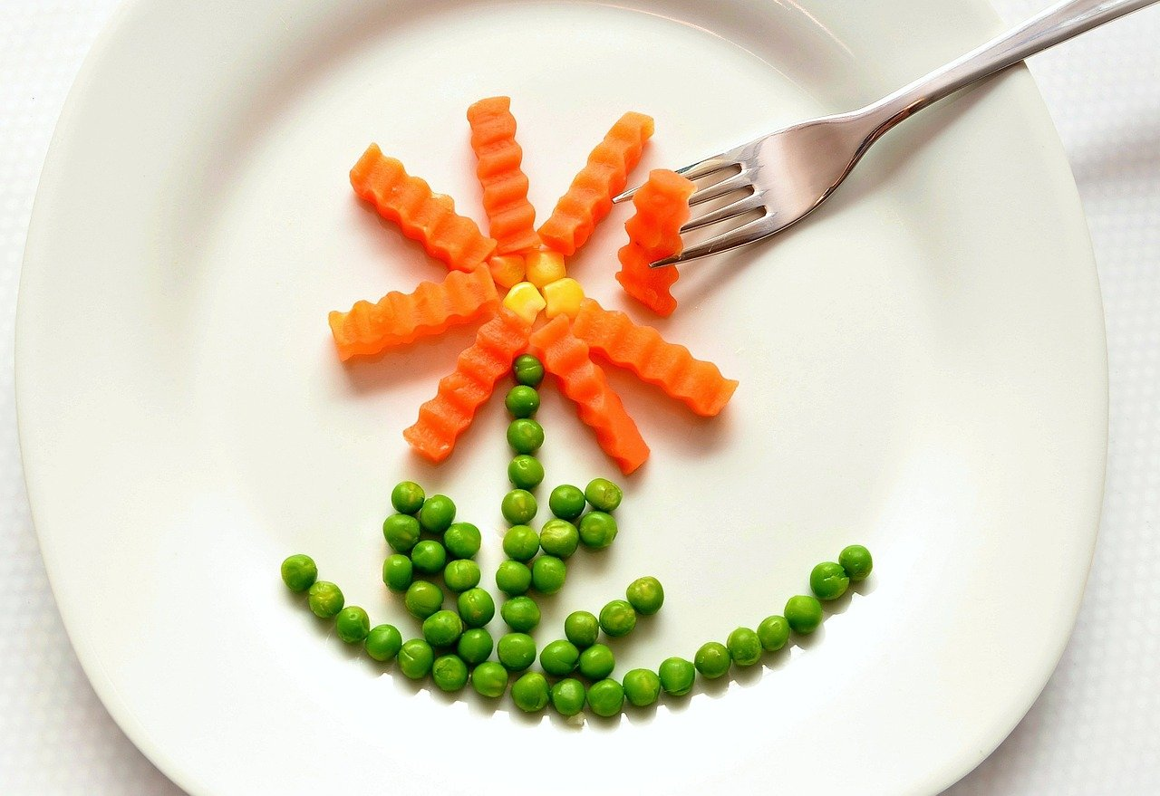 flower design made with green peas and orange carrots on a plate
