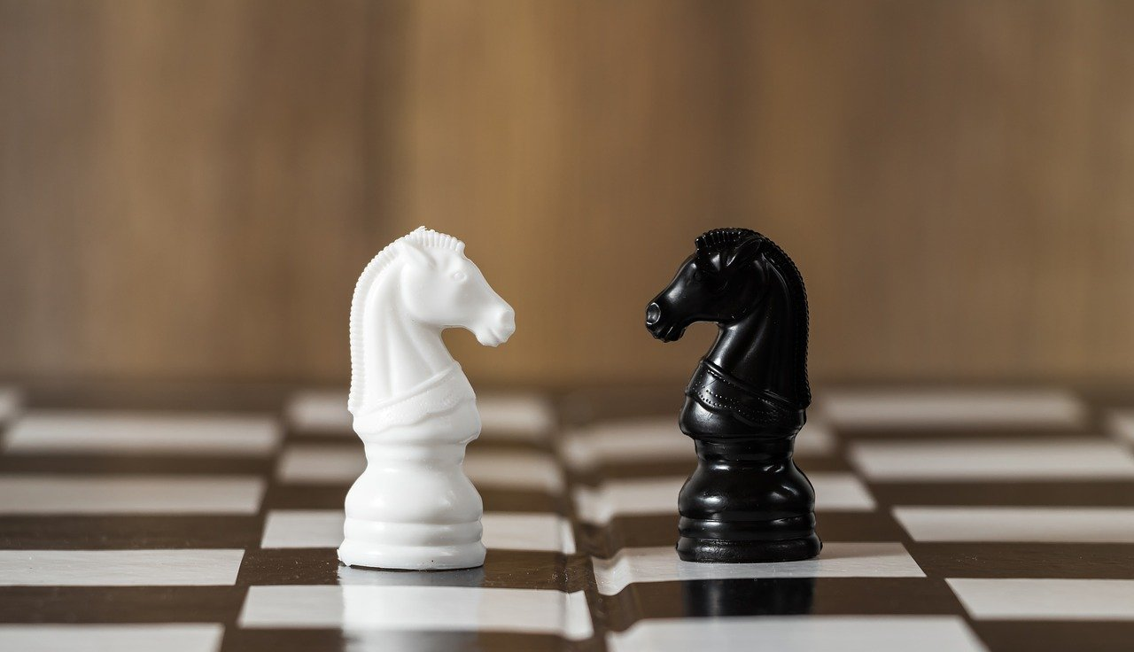 white knight and black knight facing each other on a chessboard